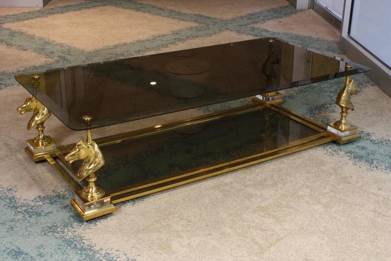 Large size French gilded bronze, brass and smokey glass two-tiered coffee table by Maison Charles (mid-20th century.) The horse heads rest on clear Lucite plinths, with double stretchers connecting them and supporting the lower glass tier. The top