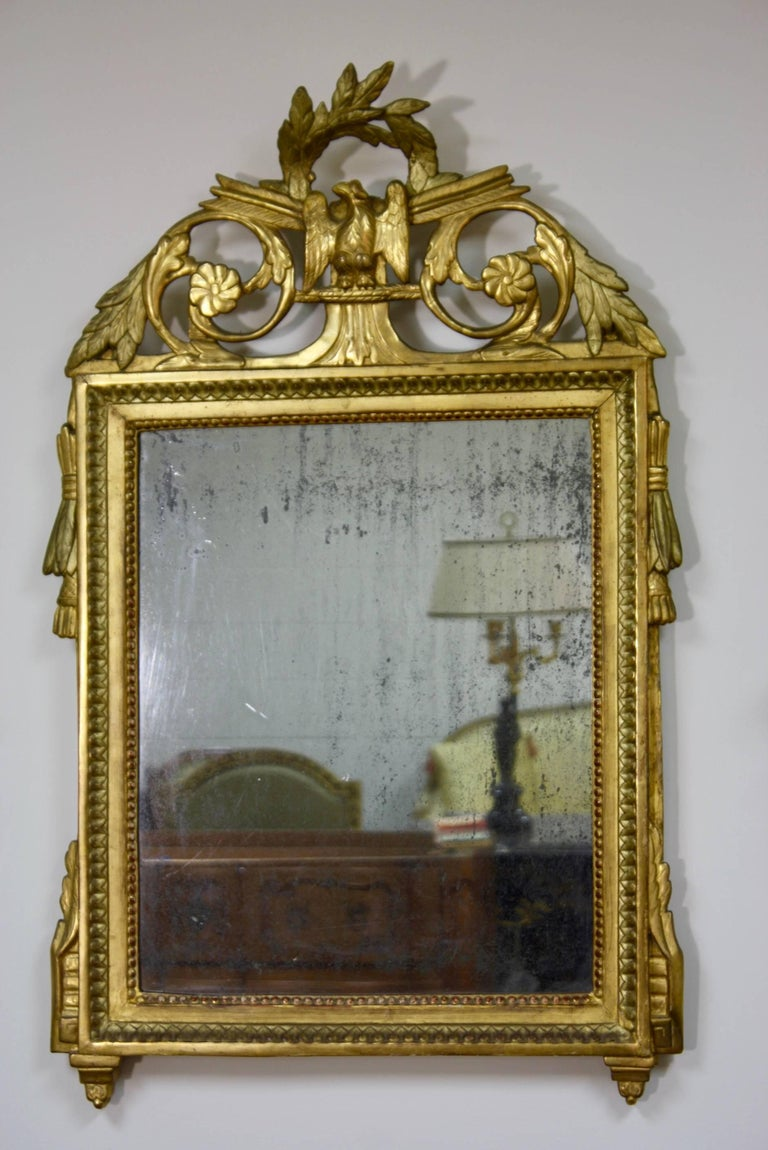 A fine quality Louis XVI period French giltwood trumeau mirror, circa 1780, with neoclassical detailing, including laurel wreath and eagle on the cartouche, original mercury glass and wooden back.