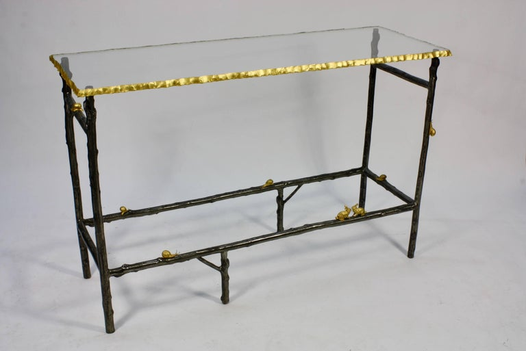 "French console table custom-made of patinated iron in the form of twigs, with gilt bronze snails and rabbits. The thick glass top (¾"") is near lead crystal quality, with hand cut rusticated and gilded edges. Due to its quality, the glass is very"