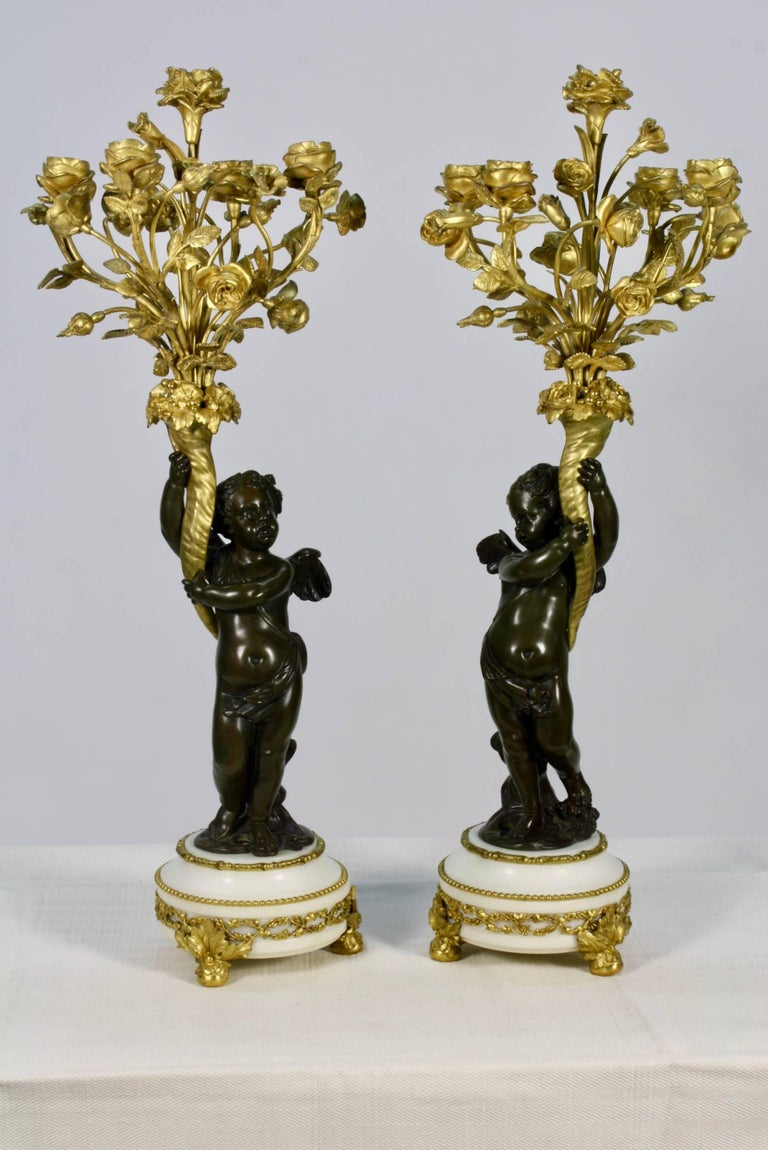 Pair of candelabra with winged putti, each supporting a floral bouquet, on top of marble base. Each putti is patinated bronze and the bouquets are gilt bronze. The floral bouquet has five candle cups. The candle cups and bases have been drilled for