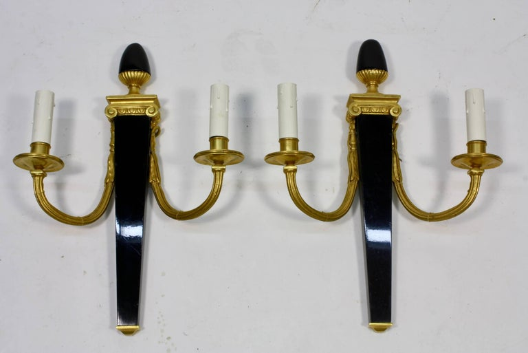 A set of four neoclassical sconces by the French manufacturer Maison Bagues. Each sconces features a black-lacquered body tapering to a gilt bronze base with an egg-from finial. The two fluted gilt bronze arms attach to an ionic style capital. Each