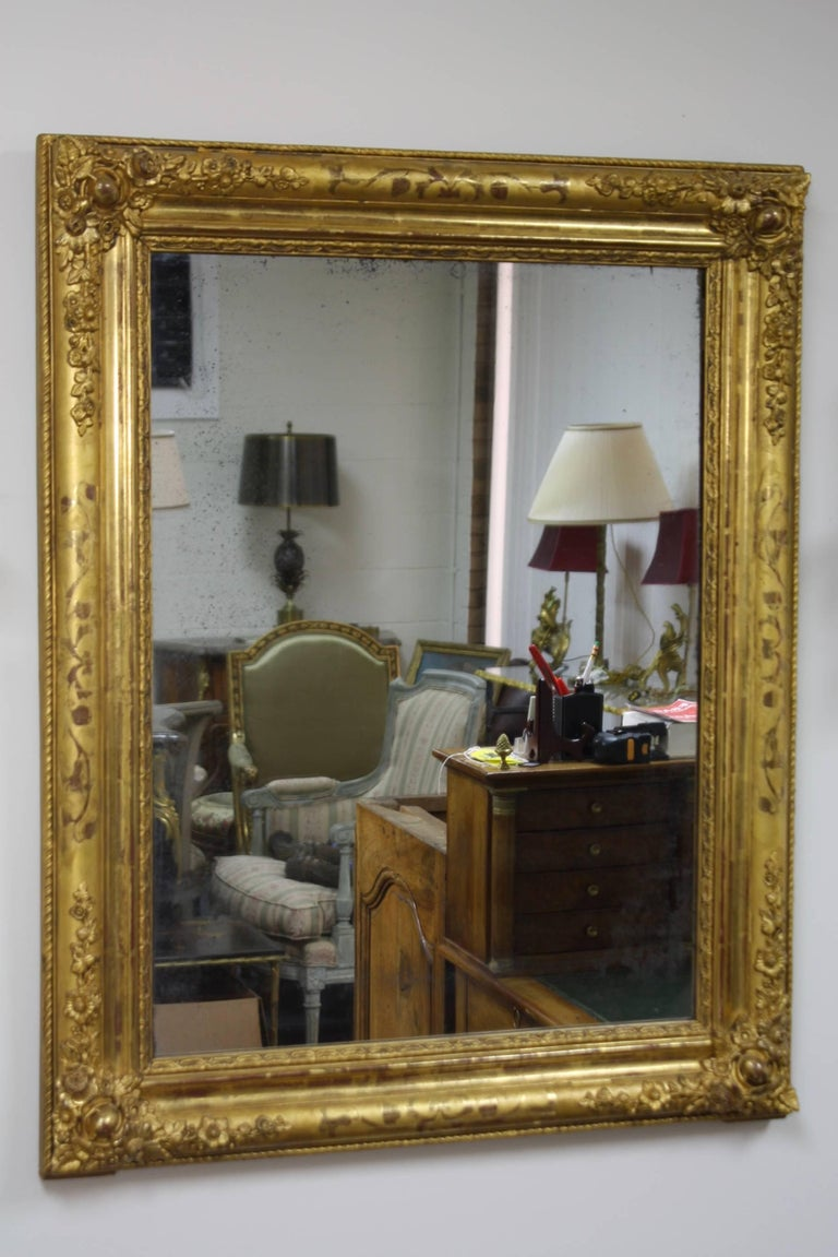 Beautiful French giltwood mirror from the Charles X period, (circa 1830). The mirror features carved floral details in the corners and vine design on the sides. Nice old mercury glass shows its age and could be original. The mirror has an old wood