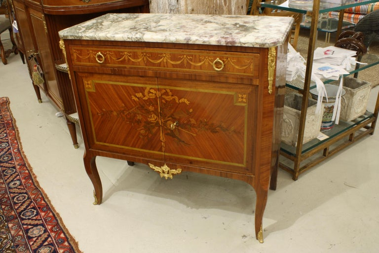 French Louis XV / Louis XVI Transitional style commode with breche violet marble top (Napoleon III period, circa 1870). This commode features floral marquetry with garden tools (rake and shovel) and rose garlands on the cabinet doors, and