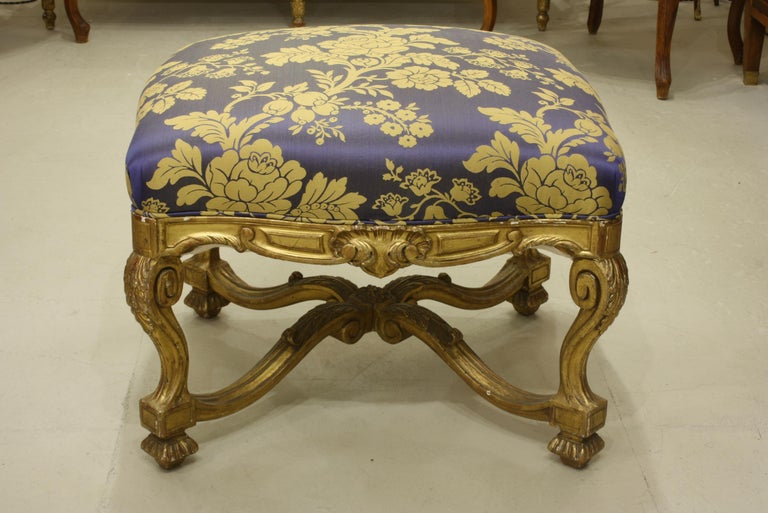 French Regence style carved giltwood stool, tabouret or ottoman with stretcher. The tabouret has been reupholstered in silk damask fabric.