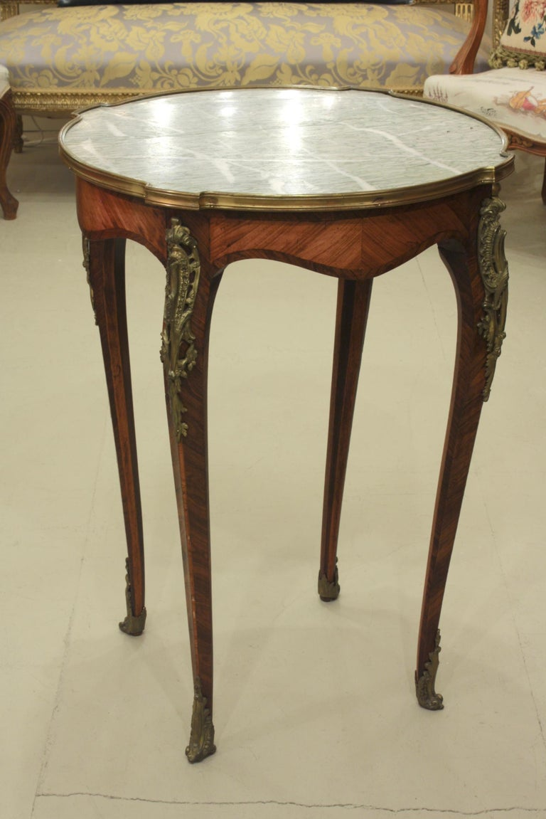 French Louis XV style gueridon or center table with nicely veined green marble top and gilt bronze mounts. The parquetry on the frieze and legs is bois de rose and bois Violette. The marble has a small crack along a vein that is not very noticeable.