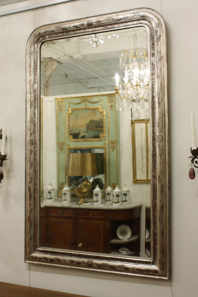 French antique Louis-Philippe mirror with silver leaf gilt frame decorated with vine and leaf design. Includes the original bevelled mirror glass, which shows some age. The silver gilt also show some spotting.