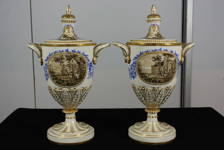 Pair of elegant 19th century Italian porcelain lidded urns with hand-painted scenes and gilded details. One side of the urns features a neoclassical scene, and the reverse side features a bucolic scene. Each of the painted scenes is framed by a