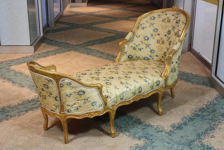 Elegant French Louis XV style giltwood chaise longue, with nicely-carved flower cartouches on the head and foot, floral carvings on the seat rail and other rococo ornaments. Upholstered in lovely silk lampas fabric (probably Tassinari) with gimp