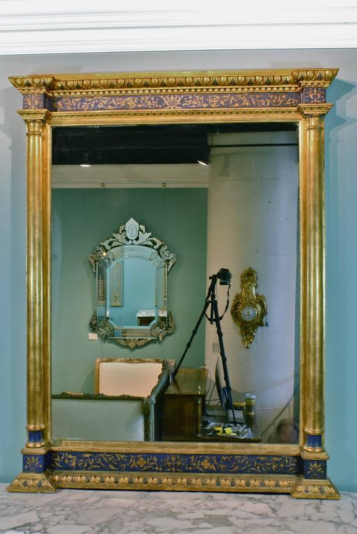 A large and unusual French blue-painted and gilded wood mirror, with finely-decorated giltwood detailing, detached giltwood columns, and egg and dart trim.