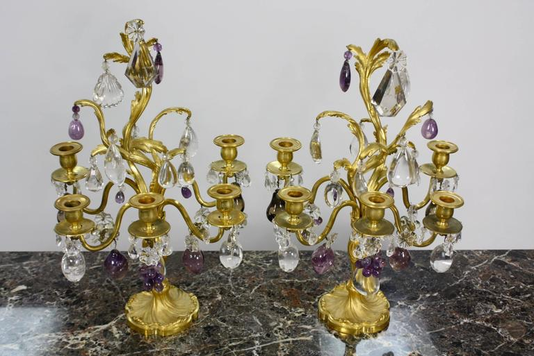 A very high quality pair of French 19th century, Louis XV style, gilt-bronze girandoles with five arms, beautiful rock crystal, including rock crystal drops in scallop form, amethyst rock crystal fruit, and pale topaz-colored crystal kites.