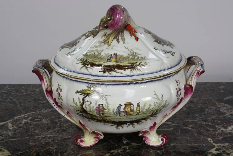 A lovely, highly-detailed French faience soup tureen, with handles, feet and nicely-sculpted vegetable decorated cover (18th century). The top cover has a radish, carrot and scallion. The painted decoration on the sides includes a shield with