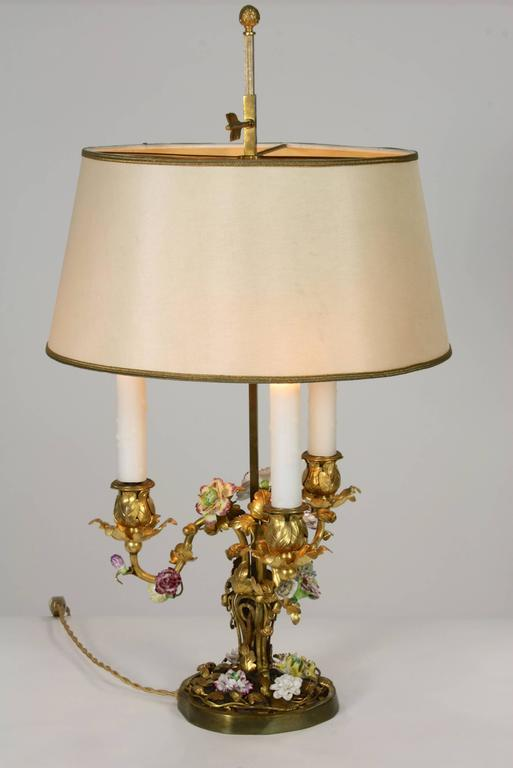 A very fine, 19th century French gilt bronze Louis XV style bouillotte lamp, in foliate form with multicolored porcelain flowers, electrified with three lights. Silk over paper adjustable shade. Napoleon III period.