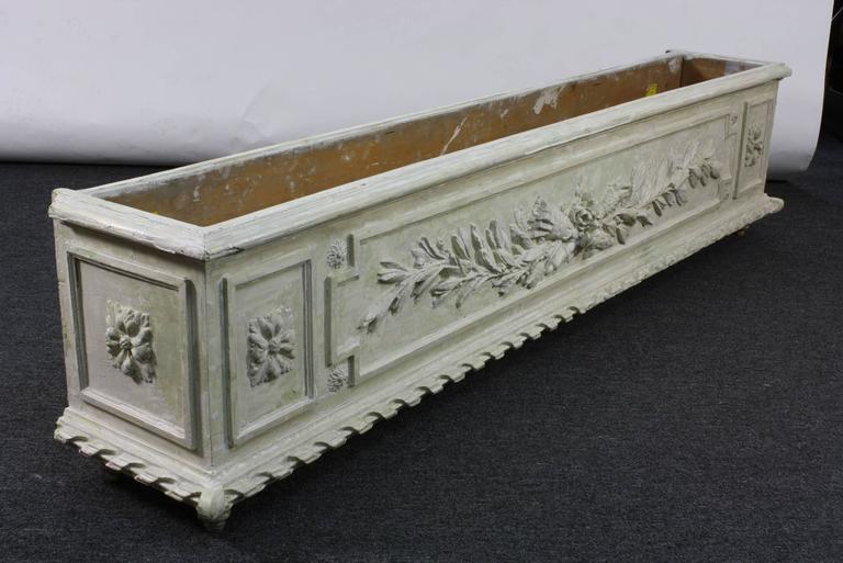 An unusually large, and deeply sculpted and painted wood planter or jardinière, in the Louis XVI style (late 19th century). The planter appears to have been stripped of some coats of paint, down to its originally grey-green paint and white gesso.