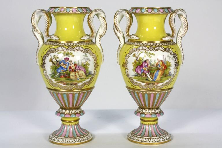 A highly-decorative pair of yellow porcelain vases, hand-painted with detailed central romantic scene, and having snake-form handles (Meissen, 19th century).