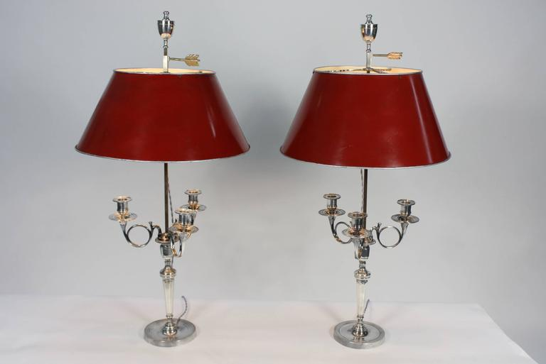 A lovely pair of neoclassical French candelabra (circa 1880), in silvered-bronze, having been converted to bouillotte lamps, with red tole shades. Each lamp has three arms for candlesticks, and the tole shade height is adjustable, decorated on top