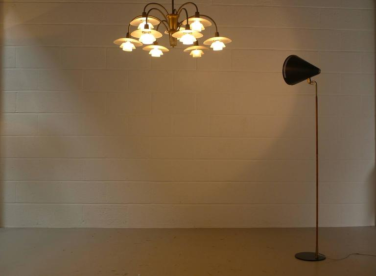"""Paavo Tynell for Idman, Finland, model K10-10 rare floor lamp, enameled metal base, brass stem with original cane wrapping , and black enameled spun aluminium perforated adjustable shade. The lever mechanism stamped by maker """"Idman"""" . All"""