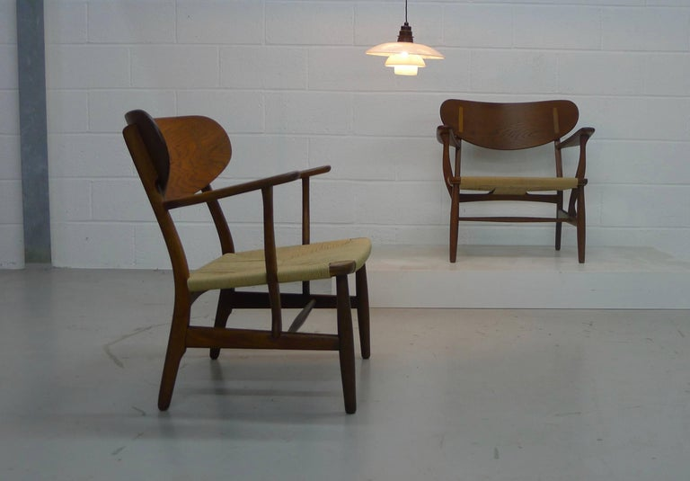 Hans Wegner, Denmark, designed 1951, a pair of CH22 armchairs of oak and paper cording. In fine vintage condition with renewed seat cords, makers mark stamped to underside of arm on both examples and one with the Danish Control tag under the other
