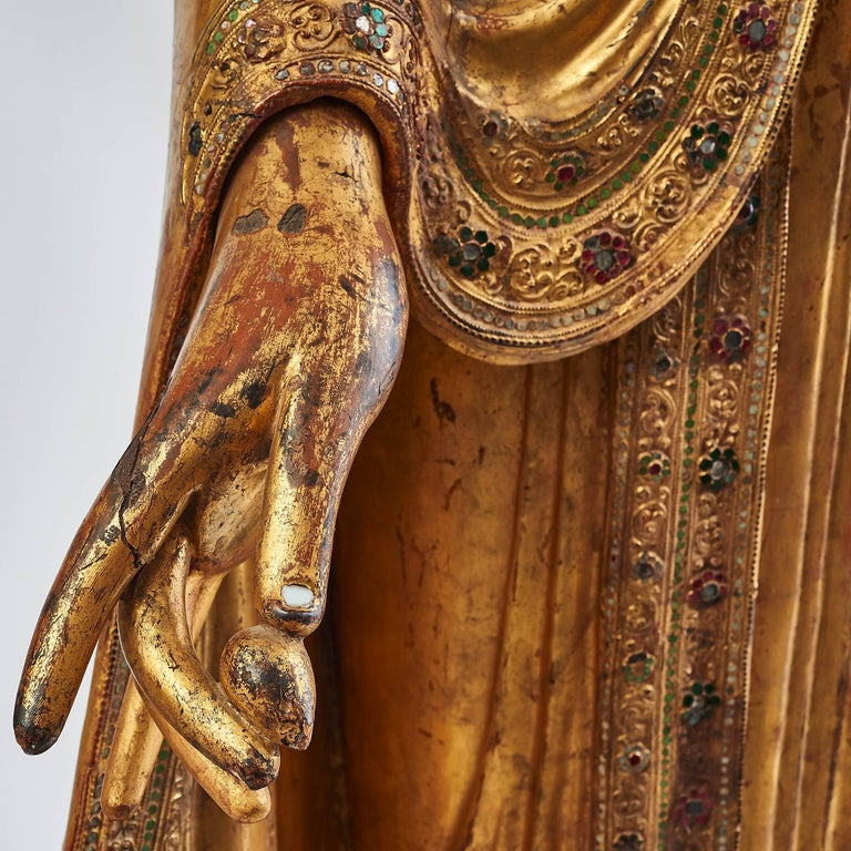 Large carved giltwood Thai standing Buddha 19th century, with a later left hand. The flowing robes encrusted with coloured glass stones forming flowers, and white glass toenails and fingernails.  The Buddha is standing on an open lotus flower in a