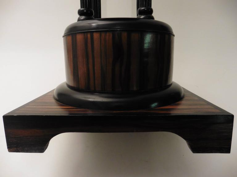 French Art Deco Macassar ebony wood table in the manner of Ruhlmann. The square base supports a round Macassar plinth, with an ebonized band. The main support is formed of four ebonized columns, finished with a simple octagonal table top, circa