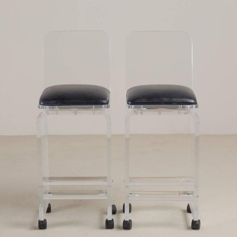 A pair of Lucite faux leather upholstered swivel bar stools, 1980s