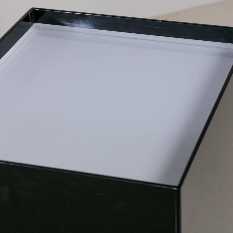 An oversized black and ivory acrylic lightbox pedestal
