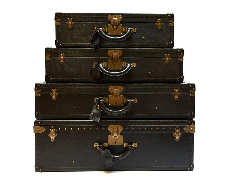 A rare set of four matching black Epi leather hard-sided luggage.  These come from the original owner, purchased in the mid-1980s. They were never used and remained stored until now. The pieces are all numbered consecutively and come with two