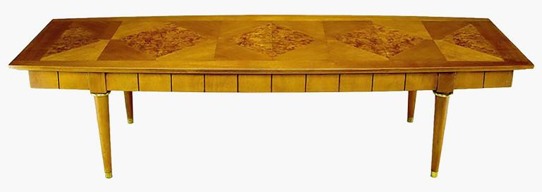 A very well crafted long coffee table in walnut with an elegant burled walnut parquetry top and incised skirt. The conical legs feature brass ferrules and sabots. Attributed to Oxford-Kent.