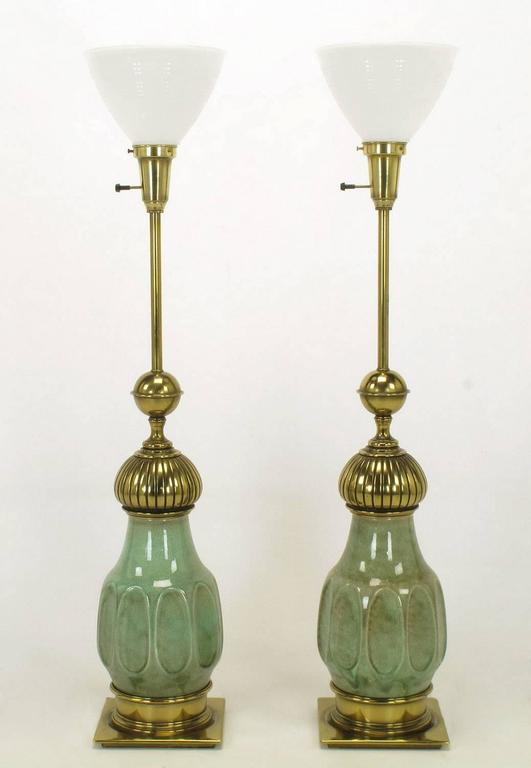 Excellent pair of brass and ceramic bodied Moorish style table lamps by Stiffel. Ceramic bodies are a mottled sea foam green crackle glazed urn form. Brass flat plinth, incised cap and ball, stem and milk glass diffuser. Sold sans shades.