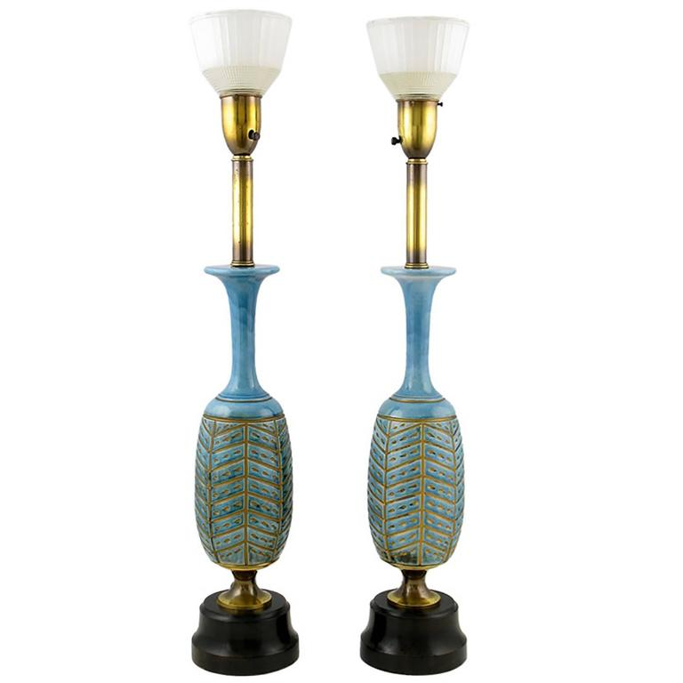 Statuesque pair of beautifully glazed baluster-form ceramic table lamps with impressed and gilt herringbone design. Ebonized wood base and original clear and milk glass diffusers. Attributed to Rembrandt Lamps, due to the style of diffuser and brass