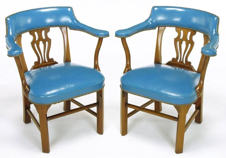 Pair of Chippendale influenced armchairs from Barnard & Simonds, Rochester, NY. Cadet blue leather wrapped arms, back as well as seat with brass nailhead details. Mahogany frames have canted front legs, Chippendale style open back and four part