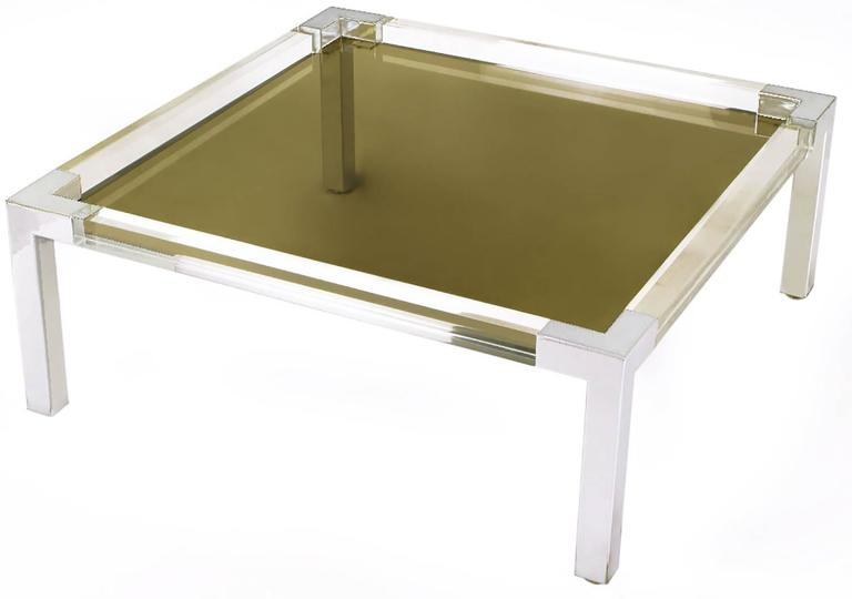 Square form coffee table with chromed metal legs and corners, Lucite side rails and recessed smoked glass top. Similar to designs by Karl Springer and Charles Hollis Jones.