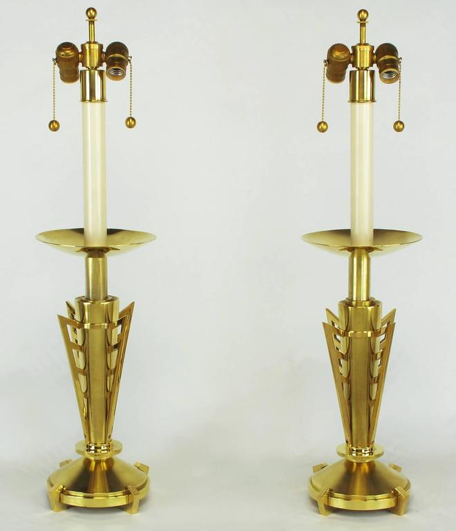 Pair of custom table lamps constructed of finely machined solid brass. Canted and polished feet on round plinth bases. Bodies are conical brushed brass with four polished brass machine age wings. Large bobeche polished on one side and brushed on