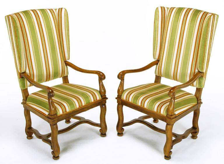 Pair of Heritage Furniture, Louis XIV inspired, winged fauteuils. Carved and patinated walnut frames with curved arms and legs with H stretchers. Original cut velvet upholstery striped in olive green, umber and taupe.