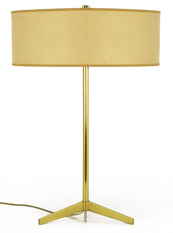 Simple and elegant brass tripod based table lamp by Lightolier. White porcelain dual sockets with white metal disc housing. Sold with drum shade and pierced top diffuser. From the period when Lightolier imported lamps by Arteluce, although we have