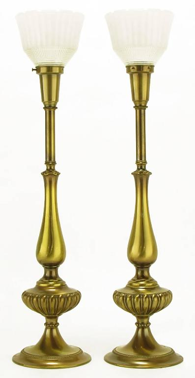 Elegant pair of solid brass Regency style table lamps from Rembrandt Lamp Company. Flanged base with egg and dart body that resembles the oil basins of pre-electric lamps. Antique lacquer finish with original glass diffuser. Sold sans shades.