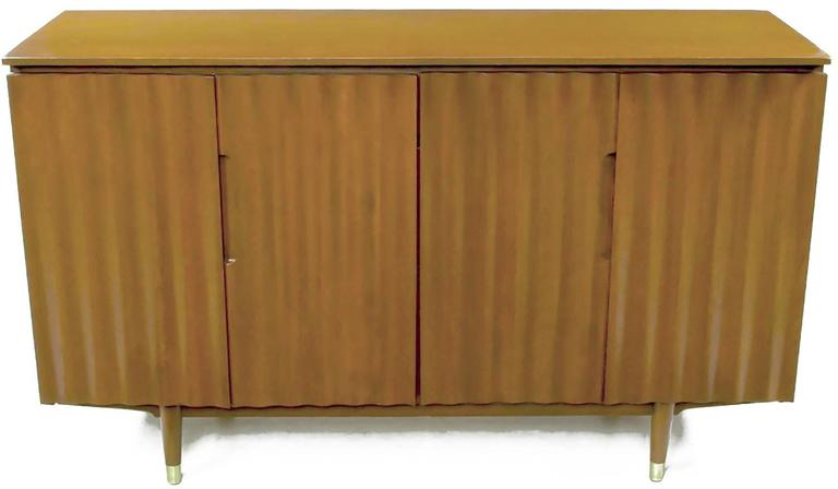 A simple yet striking sideboard in birch from the contemporary line of the Imperial Furniture Company. This modern sideboard features wave form door fronts and two semi-open front drawers. Two section shelving and brass sabots on the front legs,