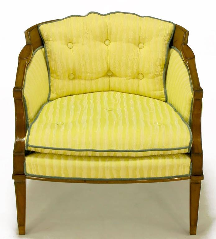 Pair of Oxford Ltd lounge chairs with carved walnut Regency frame. Saber front and back legs with nicely detailed arms and back. Fixed button tufted back cushion, loose seat cushion in a saffron striped linen and silk blend upholstery, with