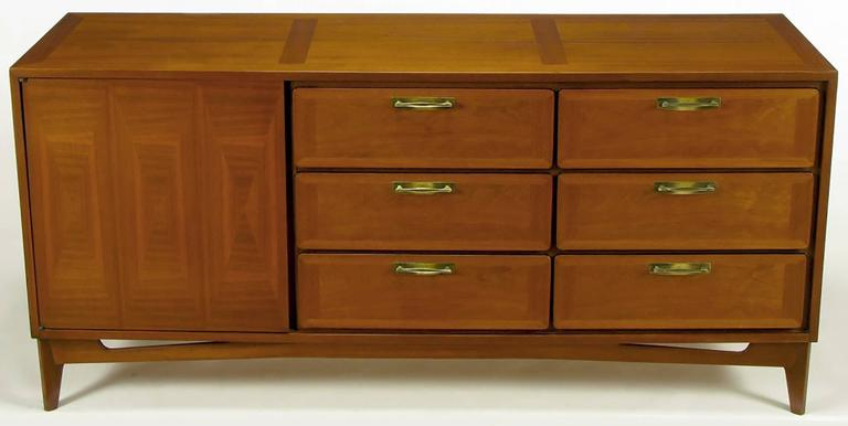 Excellent build quality and design for this, circa 1950s modern nine-drawer long dresser. Beautifully wood grained mahogany parquetry front door that opens to reveal three sliding drawers. Six additional parquetry front drawers have patinated brass