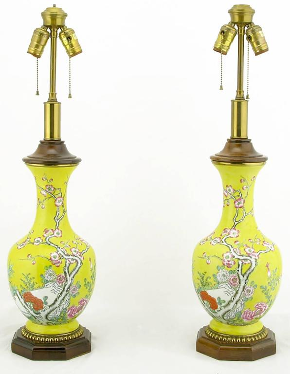 Vase form chinoiserie table lamps by Paul Hanson. The bodies are comprised of a vibrant yellow glazed ceramic vase with hand painted floral detail. The base is carved wood, with gilt egg detail. Cap is also carved wood over a brass neck. Adjustable