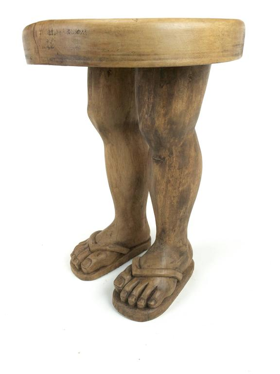 Hand-carved solid wood Folk Art stool in the shape of two legs, sandaled feet and thick wood disc seat.