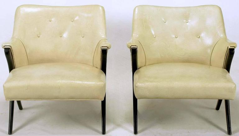 Pair of 1940s modernist club chairs in original bone glazed leather upholstery. Ebonized mahogany arms and legs in a distinctive Y shape. Brass nailhead accents. One chair has bottom welt and one does not. Possibly the inspiration for the Karpen Co.
