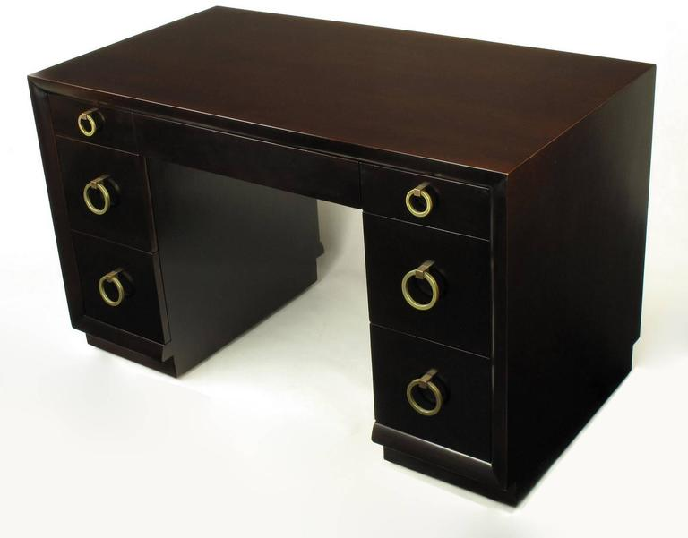 Excellently restored knee hole desk or writing table , model no. 317, by T.H. Robsjohn-Gibbings for Widdicomb. Drop ring pulls are plated in brass and the original patina has been burnished but not polished out gloss brass. The desk back is engraved