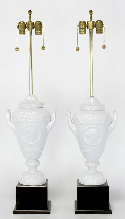 Fine pair of white German porcelain urn form table lamps with black lacquered wood plinth bases. Urn body is comprised of three parts with the flanged base, handled urn body, and bell shaped top being a separate pieces. Brass stem and Dual socket