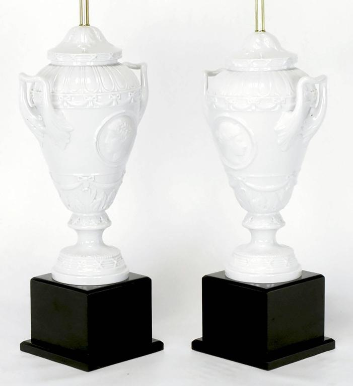 Lacquered Pair of White Porcelain Urn Table Lamps with Male and Female Busts in Relief For Sale