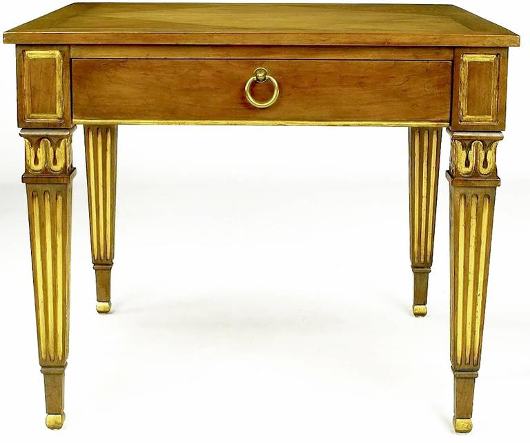 These outstanding walnut side tables from Baker feature diamond pattern parquetry inlaid tops and parcel-gilt fluted Louis XVI style legs. A single drawer is accessed by a brass drop ring pull. An exquisitely designed pair.