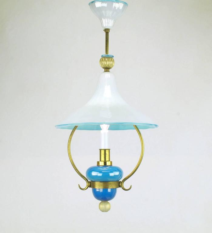 Exceptional handblown Italian Murano cased glass pendant light with brass frame. Blue and white cased glass canopy, hooded shade and body with gold flecked finals to the top and bottom. Made to look like a vintage kerosene light, this has been wired