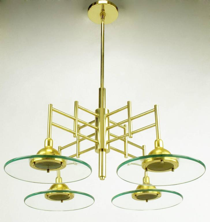 Brass four-light pendant chandelier with thick glass plate shaped shades. The glass shades magnify the amount of light making this a brighter than expected light. The frame of this chandelier is an architectural brass four arm structure with center