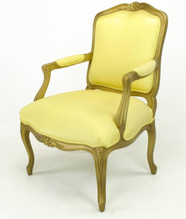 1940s giltwood Louis XV style armchair with saffron silk upholstery. Carved wood frame has been restored and gilt with black glaze. Arm height is 24.5