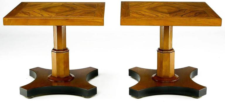 Beautifully figured walnut tops and walnut pedestals with inverted quatrefoil walnut base creates a stunning pair of side table from Baker Furniture. The base sides are accented by a satin black lacquer finish. Would make a striking two part coffee