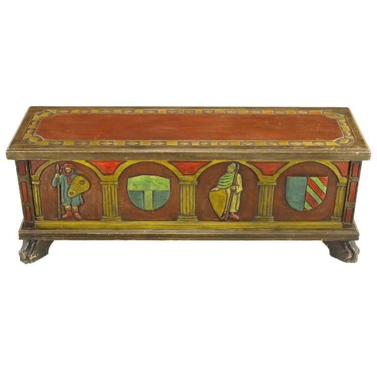 Artes De Mexico hand-painted blanket chest or trunk. Spanish Revival themes of familial crests and warriors are carved into the wood front, back and sides and hand-painted. Top has a carved and hand-painted border with a scarlet center as well as a